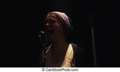 Scrubwoman with mop sing into microphone on stage of empty club, take off hat