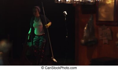 Scrubwoman with mop and bucket turn music on in empty club...