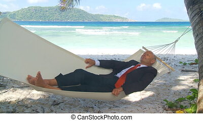 senior businessman relaxing in hammock on tropical beach