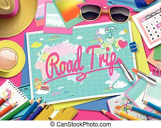Road Trip on map, top view of colorful travel essentials on...