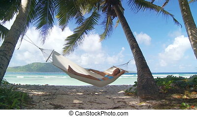 nap in paradise - young woman sleeping in hammock under...