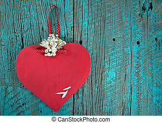red wood heart on turquoise wood - Red wooden heart with...