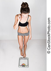 young sports woman is afraid to step on the scales