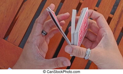 Closeup Conjurer Hands Shuffle Cards for Trick above Table -...