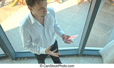 Conjurer Throws Catches Card from Pack by Window - european...