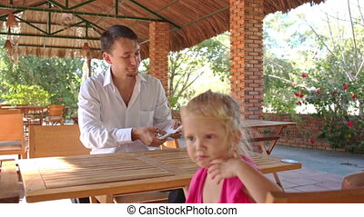 Conjurer Shows Card Pack Trick to Little Girl at Table -...