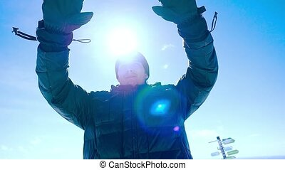 Young happy man snowboarder rises hands in Mountain sin...