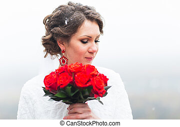 winter bride holding bouquet of red roses