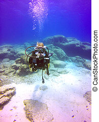Scuba diver - A young scuba diver lady swimming underwater....