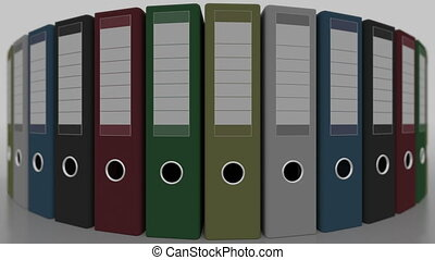 Rotating multicolored office binders, shallow focus. 4K...