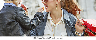 mother and daughter near Arc de Triomphe eating macaroons -...