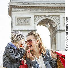 happy mother and daughter in Paris, France eating macaroons...