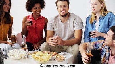 friends with drinks and snacks talking at home - friendship,...