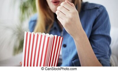 happy woman eating popcorn and watching tv at home -...