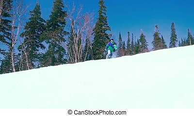Young snowboarder downhill in slowmotion, snow-capped...