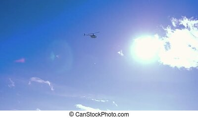 Helicopter flying in the blue sky with sun in slowmotion....
