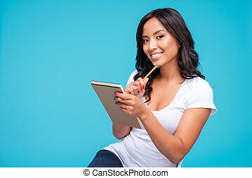 Asian woman thinking about something and holding notebook -...