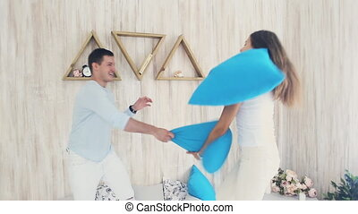 Happy couple in pillow fight