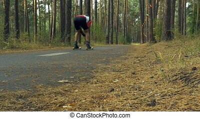 riders on ski-rollers in forest. athletes to compete in...