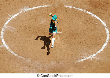 A softball player pitches her ball from the mound in a large...