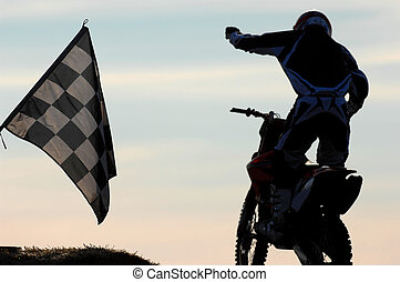 A motocross competitor crosses the finsh line