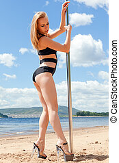 blonde dancer in bathing suit and high heeled shoes on...