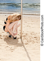 dancer fastening high heeled shoes near pole on background...