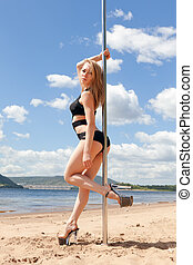 blonde dancer near pole in bathing suit and high heeled...