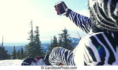 Snowboarder man in suit of kigurumi of zebra take selfie with phone over mountains in slowmotion on the sun background with lens flare effects. 1920x1080