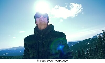 Portrait of smiling man in the blue skiing glasses against cloudy blue sky with the sun in slowmotion. 1920x1080