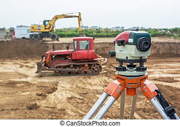 Theodolite on tripod at construction site with excavators...