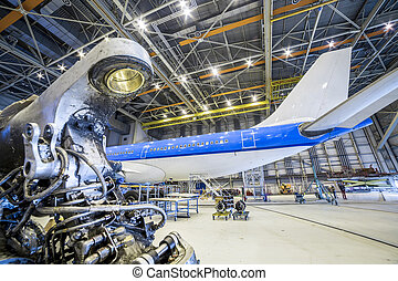 Refurbishment of an airplane in a hangar. - Refurbishment of...