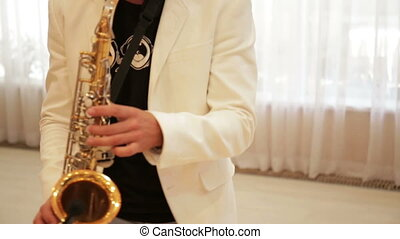 A man plays the saxophone - Man playing saxophone on...