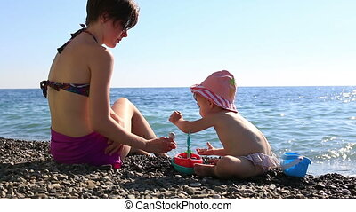 happy young mother playing with her child on the beach on a background of blue sea. Full HD. 1920x1080