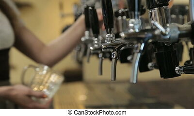 Bartender pours a beer from the beer tap in the pub