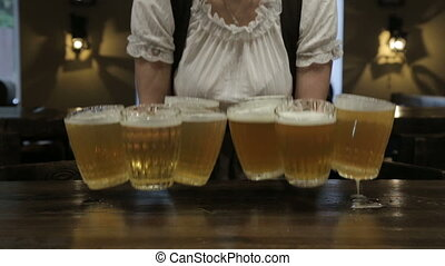 Waitress puts a full beer mugs on the table in the pub