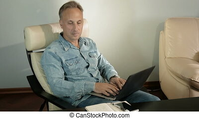 Man working with a laptop, sitting in the armchair