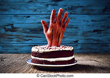 cake topped with a bloody hand for halloween - a red velvet...