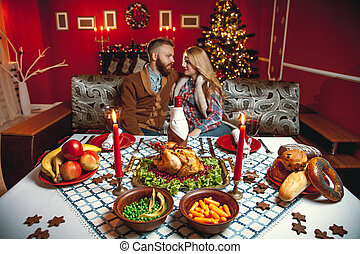Beautiful couple in a decorated room with a Christmas tree....