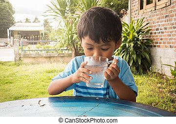 Cute little boy drinking water in the park