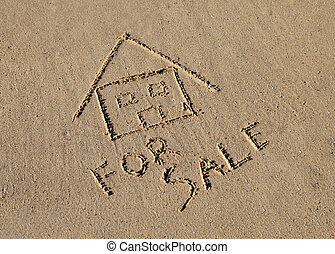 "A ""beach house\"" for sale drawn in the sand at the beach"