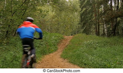 Teen rides a bike through the woods It overcomes the hill