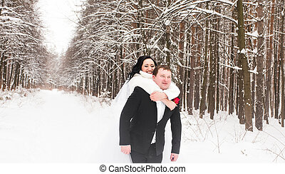 Man giving woman piggyback ride on winter vacation in snowy forest.
