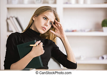 Girl with notepad thinking at workplace - Portrait of...