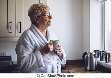 Senior Woman Looking out Window - Senior woman looking out...