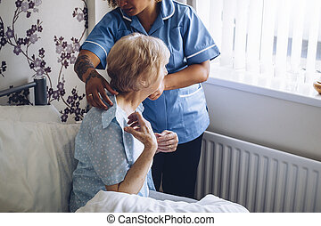 Home caregiver dressing senior