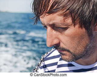 Bearded pensive male looking at the sea from yacht,...