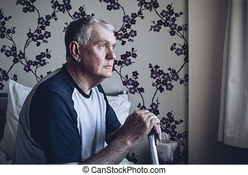 Senior Man Lost in Thought - Senior man sitting on his bed....