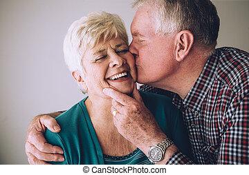 Senior man kissing wife on cheek - Senior man kissing his...