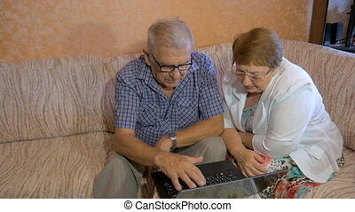 Beautiful couple at the age of working on the laptop at...